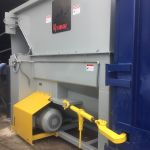 Auger-Pak™ EM-60W, Open at a Dock Platform, Rear Feed Flip Hopper, Forklift and Hand-fed, with Attached Container, Outside View