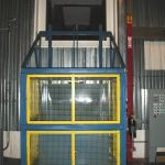 Quad-Shaft Electromechanical Shear Shredder, Auger-Pak™ EM-15G, installed inside view of vertical lift cart tipper and chute opening.